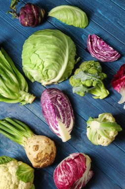Different types of cabbage on color wooden background