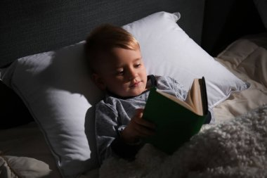 Cute little boy reading book in bed at home