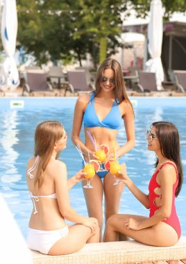 Beautiful young women in swimming suits drinking cocktails near pool on summer day