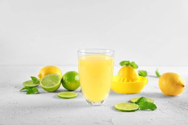 Glass of fresh lemon juice and slices of lime on white textured background