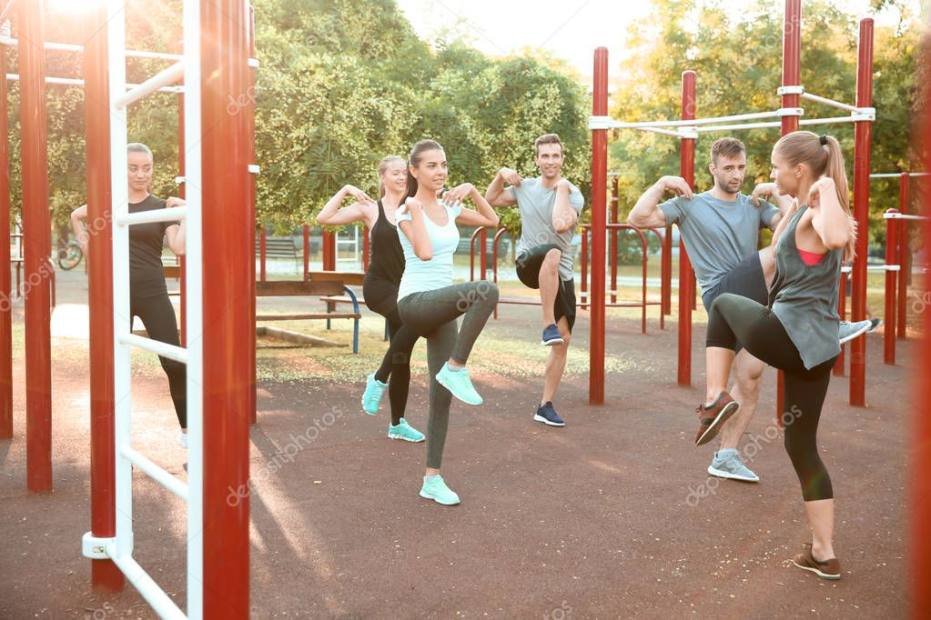 Group of sporty people training on athletic field outdoors