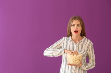 Emotional young woman with bowl of popcorn on color background