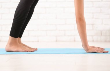 Sporty young woman practicing yoga on mat indoors