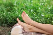 Lábakkal pihenő parkban kockás a fiatal nő
