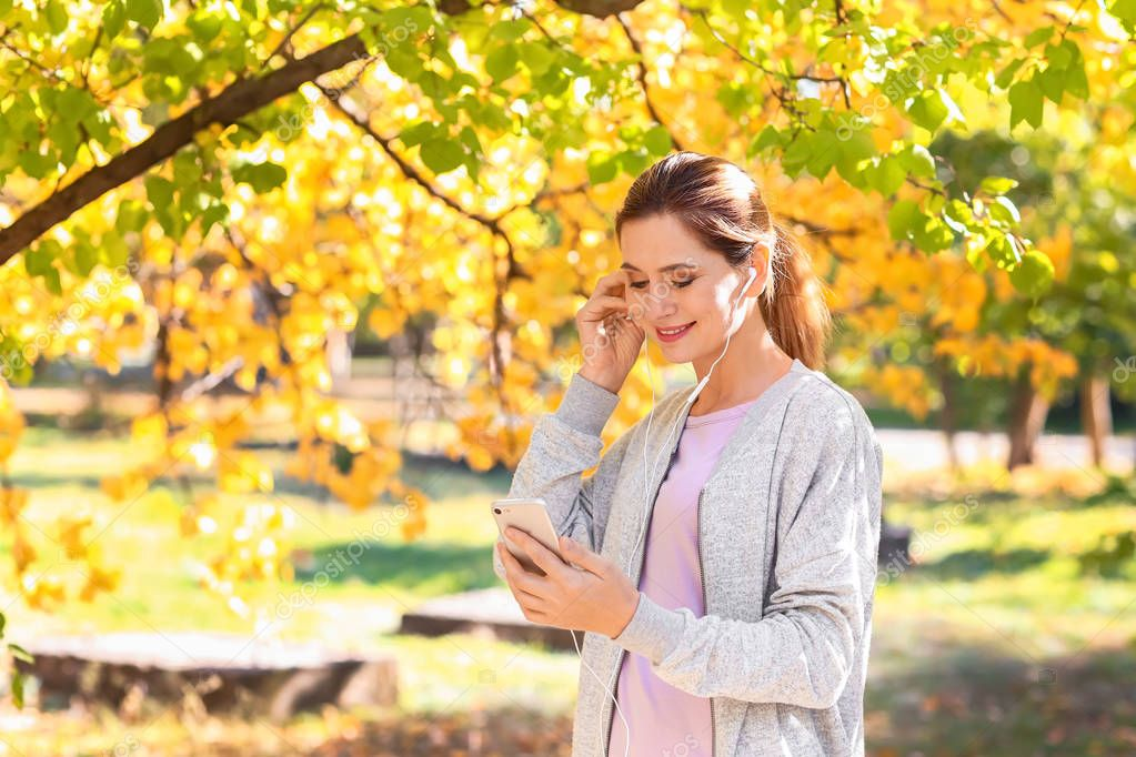 Sporty woman listening to music in autumn park