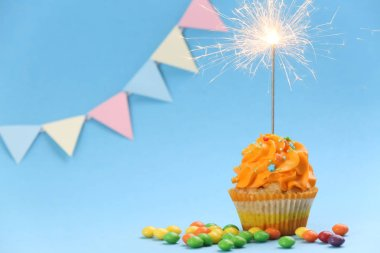 Tasty birthday cupcake with sparkler on color background
