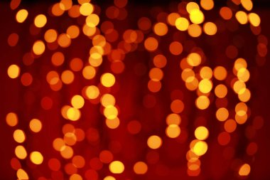 Glowing Christmas lights on color background, blurred view