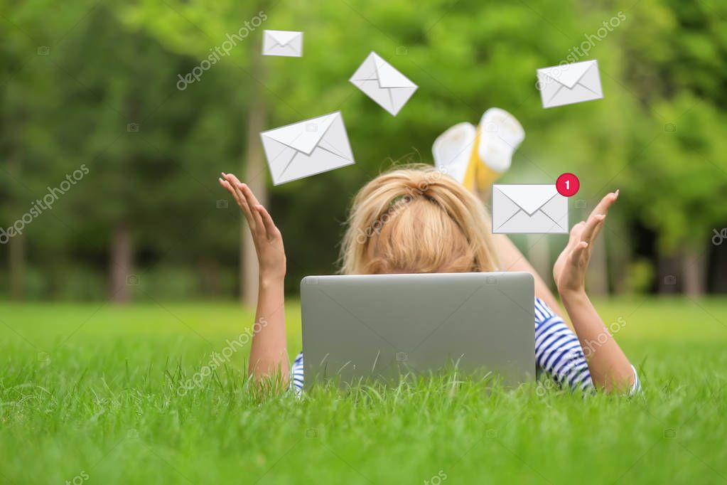 Young woman with laptop checking an email in park