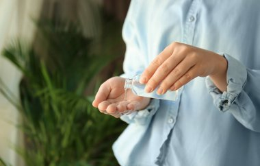 Woman using antibacterial hand gel, closeup