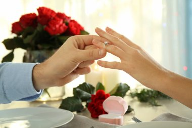 Young man putting engagement ring on fiancee's finger at romantic date
