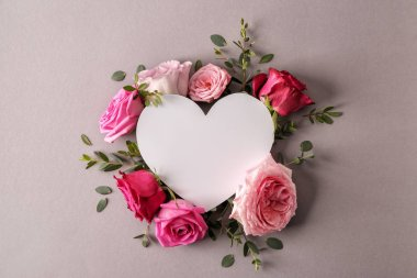 Heart shaped card with beautiful roses on grey background