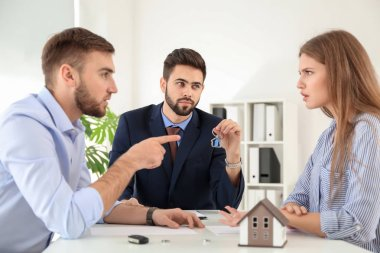 Unhappy couple dividing marital property in office of divorce lawyer