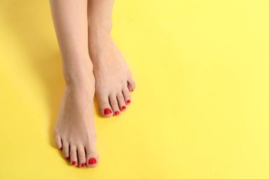 Female legs with beautiful pedicure on color background