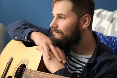 Bearded man with guitar at home