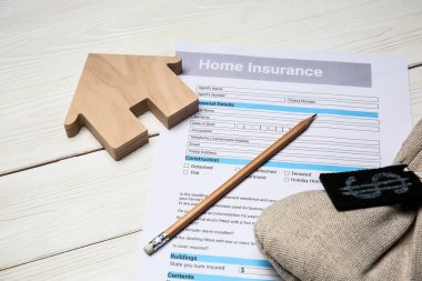 Home insurance form with money bag on white table