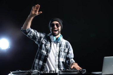 Male DJ playing music on dark background