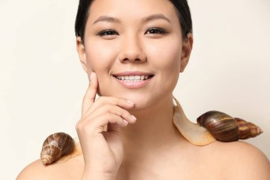 Asian woman with giant Achatina snails on white background