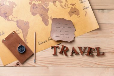 Notebook, old paper sheet, compass and world map on wooden background. Travel concept