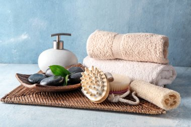 Massage brushes with towels and spa stones on table