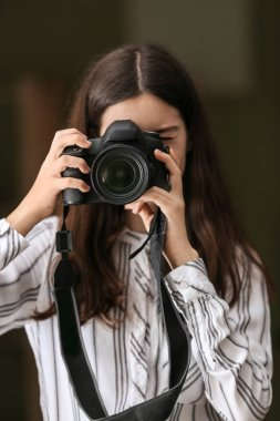 Young girl with modern photo camera at home