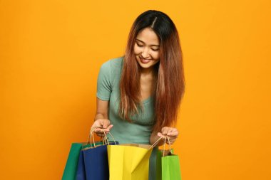 Asian woman with shopping bags on color background