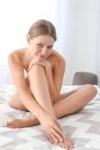 schöne junge Frau nach Laser-Haarentfernung der Beine zu Hause