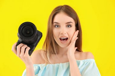 Confused female photographer on color background