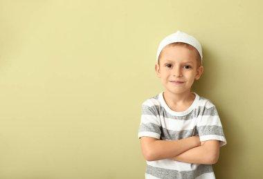 Little Muslim boy on color background