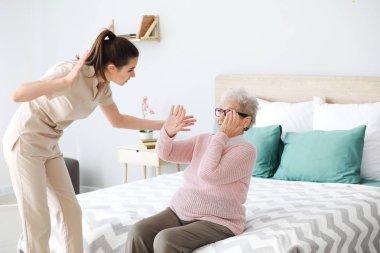 Caregiver mistreating senior woman in nursing home