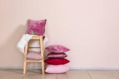 Stool with soft pillows near light wall