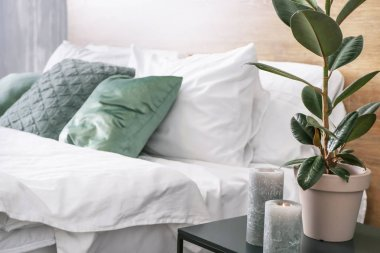 Table with green plants and candles near bed in room