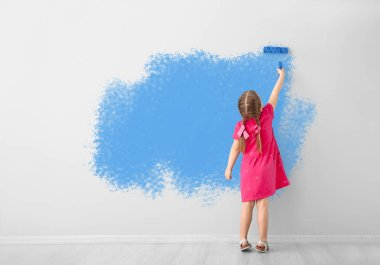 Little girl painting wall in room