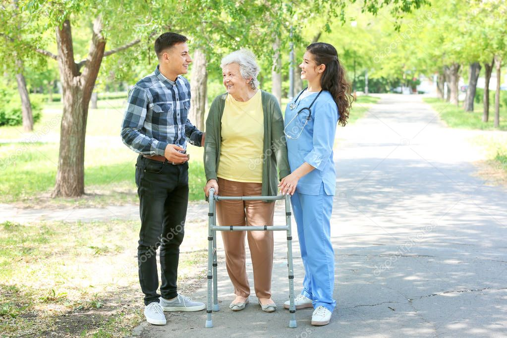 Caregiver and grandson walking with senior woman in park
