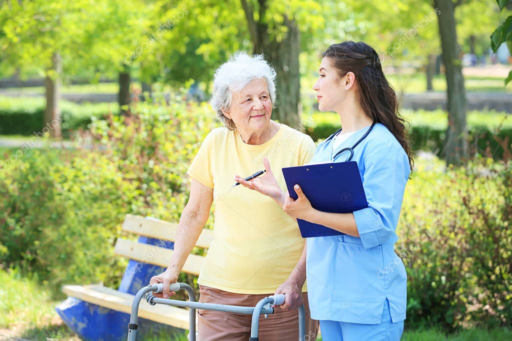 Caregiver walking with senior woman in park