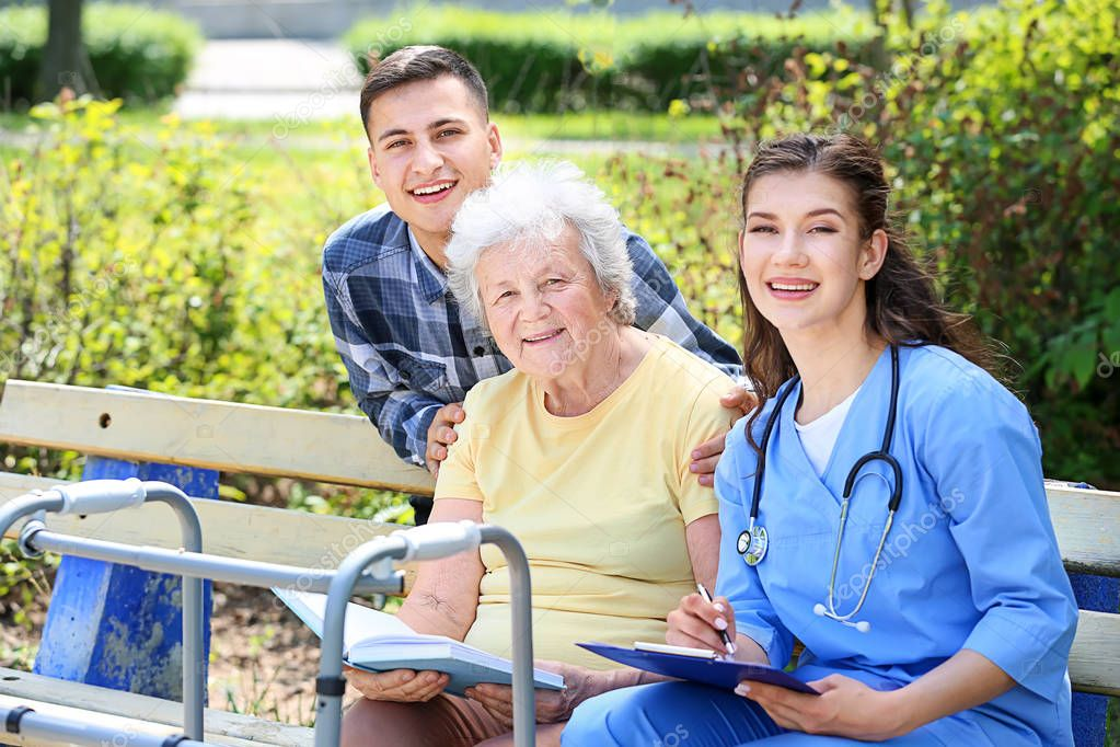 Caregiver and grandson with senior woman in park