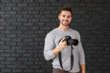 Young male photographer on dark background