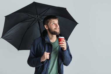Handsome man with umbrella and cup of coffee on white background