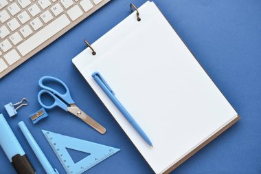 Composition with stationery and computer keyboard on color background
