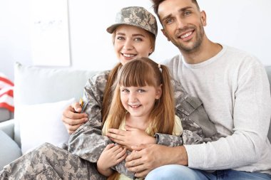 Happy female soldier with her family at home