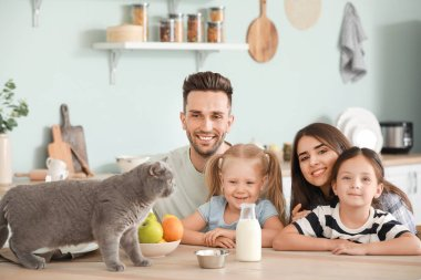 Happy family with cute cat in kitchen