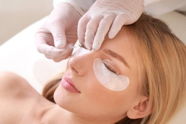 Young woman undergoing procedure of eyelashes lamination in beauty salon