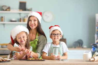 Woman and her little children preparing Christmas cookies at home