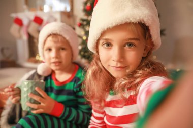 Cute little children in Santa Claus hats taking selfie at home