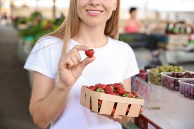 Woman with fresh strawberries in basket at market