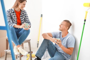 Happy young couple resting during repair of their new house