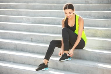Sporty young woman tying shoelaces outdoors