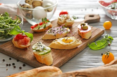 Board with different tasty sandwiches on wooden table