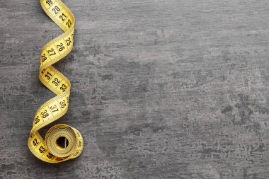 Measuring tape on grey background