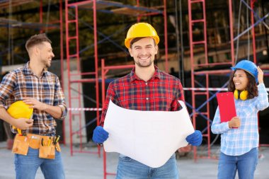 Portrait of male architect with his team in building area