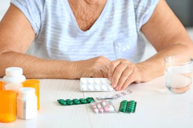 Elderly woman with medicines at home, closeup